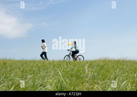 Junge Frau Reiten Fahrrad hinter jungen Männer laufen - Stockfoto