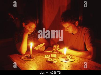 Paar Spielkarten in einer Backcountry-Hütte bei Kerzenschein Neuseeland - Stockfoto