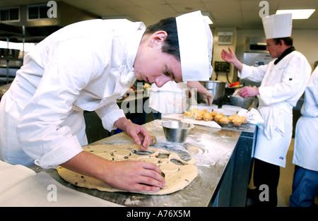 Junger Mann studieren catering macht Gebäck in einer Klasse in einer modernen Küche - Stockfoto