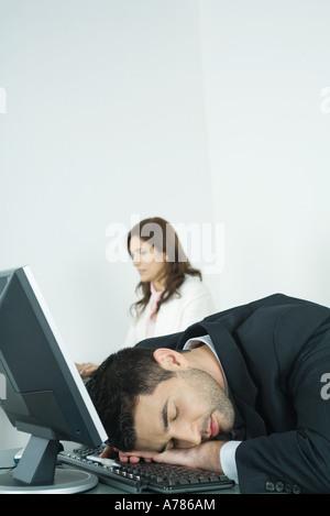 Geschäftsmann, schlafen auf Tastatur, während die Kollegen im Hintergrund arbeitet - Stockfoto