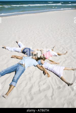 Familie auf Sand, Köpfe zusammen und Arme und Beine - Stockfoto