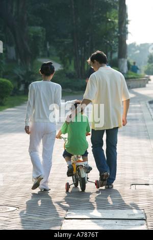 Eltern, die zu Fuß neben Sohn auf dem Fahrrad mit Stützrädern, Rückansicht - Stockfoto