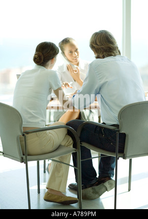 Junges Paar sitzt über Tabelle von weiblichen Berufseinsteiger mit Telefon - Stockfoto