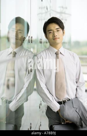 Geschäftsmann Glaswand gelehnt, Porträt - Stockfoto