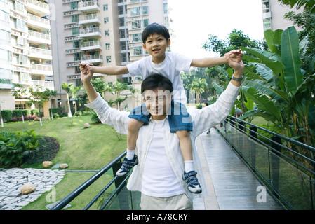 Junge Reiten auf Vaters Schultern, Vorderansicht, lächelnd in die Kamera - Stockfoto