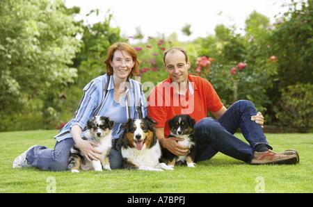 Frau und Mann mit Australian Shepherd einen Welpen auf Wiese - Stockfoto