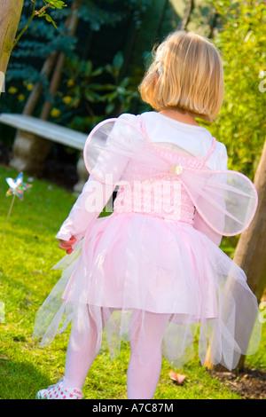 Junges Mädchen gekleidet als Fee, im Sommergarten mit Rücken zur Kamera laufen - Stockfoto