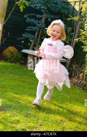 Junges Mädchen gekleidet als Fee, im Sommergarten in Richtung Kamera laufen - Stockfoto