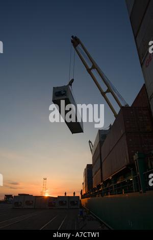 Entladung Container bei Sonnenuntergang vom Schiff in den Hafen von Caldera Costa Rica Republik Zentralamerika Silhouette - Stockfoto