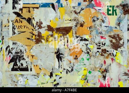 Wand bedeckt mit bunten Stücke zerrissenes Papier Reste von Bulletins entfernte Plakate und Werbung - Stockfoto