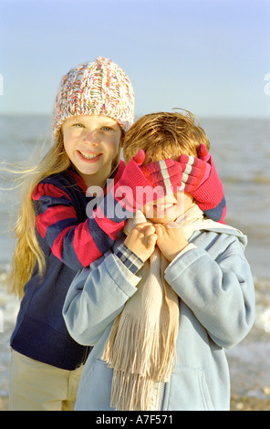 Junges Mädchen mit den Augen eines kleinen Jungen beim Spielen am Strand - Stockfoto