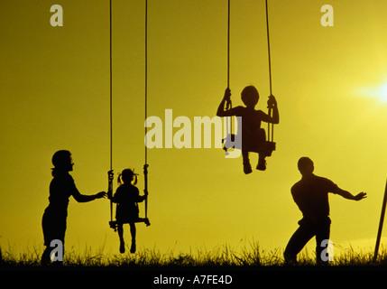 Silhouette der Familie mit kleinen Kindern beim Spielen auf Schaukeln bei Sonnenuntergang - Stockfoto