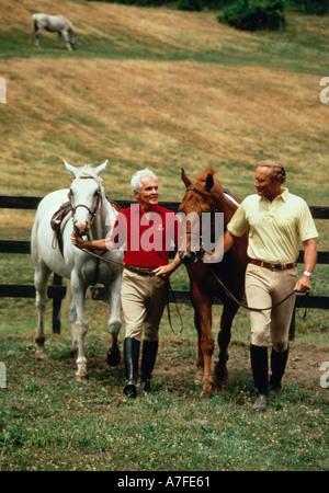 Zwei Männer, die ihre Pferde gehen, obwohl ein Feld - Stockfoto