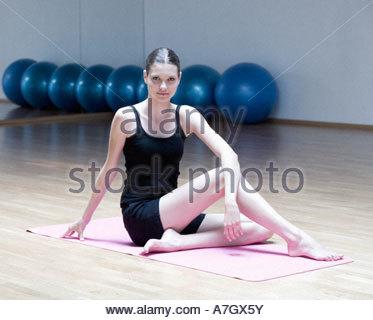 Eine junge Frau sitzt auf einer Yogamatte - Stockfoto