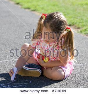 Junges Mädchen schreiben mit Kreide auf dem Spielplatz - Stockfoto