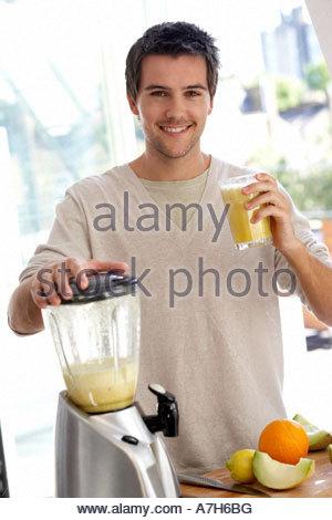 Junger Mann bereitet frische Fruchtsäfte - Stockfoto