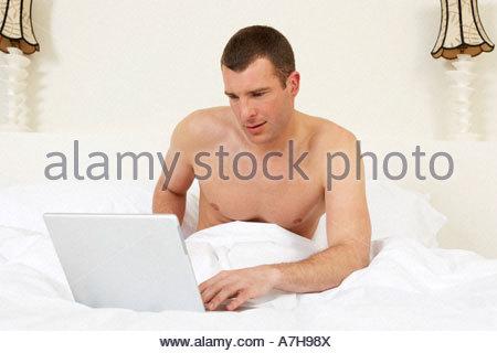 Junger Mann im Bett, am Laptop arbeiten - Stockfoto