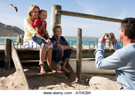 Eine Familie sitzt am Strand, Vater Aufnahme - Stockfoto