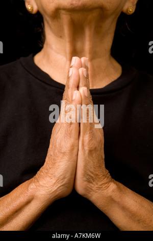 Eine alte asiatische Frau hält ihre Hände im Gebet - Stockfoto