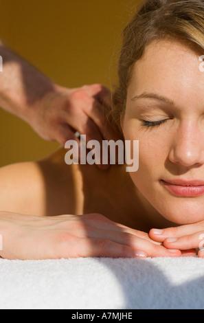 Junge Frau mit Augen geschlossen empfangenden massage - Stockfoto