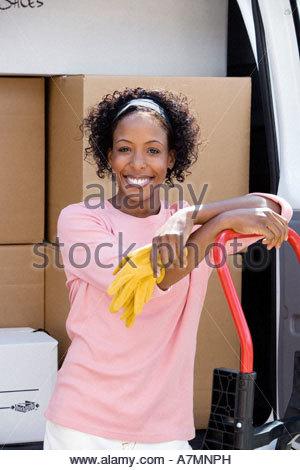 Frau Haus stehen neben van in Einfahrt gelehnt Dolly lächelnd Porträt auf Seite verschieben - Stockfoto