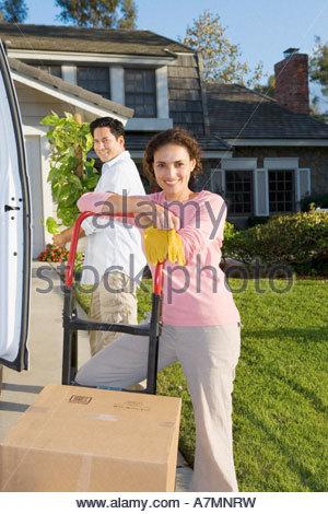 Paar bewegen Haus Mann neben van mit Topf Pflanze Frau gelehnt auf Seite Dolly, Lächeln, Porträt - Stockfoto