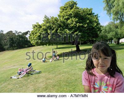 Mädchen 7 9 stehen auf dem Rasen im Park Freunde spielen in der Nähe Fahrräder Fokus auf Vordergrund Porträt - Stockfoto