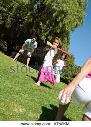 Zwei-Generationen-Familie spielen Softball im Park Mädchen 6-8 lächelnd Neigung zu zucken - Stockfoto