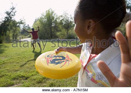 Mädchen 11 13 Spielen Frisbee mit Vater im Park lächelnd Nahaufnahme Rückansicht - Stockfoto