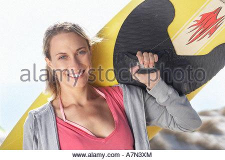 Junge Frau tragen gelbe Surfbrett auf Schulter am Strand Nähe Lächeln, Porträt - Stockfoto