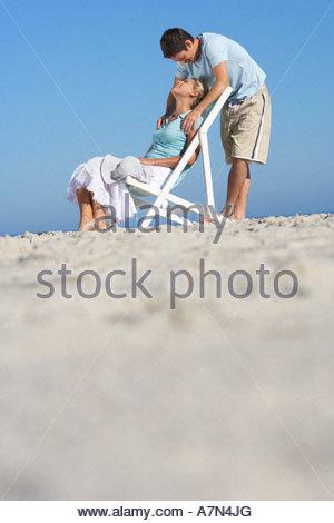 Paar am Sandstrand Mann steht hinter Frau im Liegestuhl Oberfläche Ebene entspannen - Stockfoto