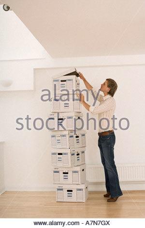 Geschäftsmann, die neben hohen Stapel von Datei-Boxen in leeres Büro Deckelöffnen-Top-box - Stockfoto