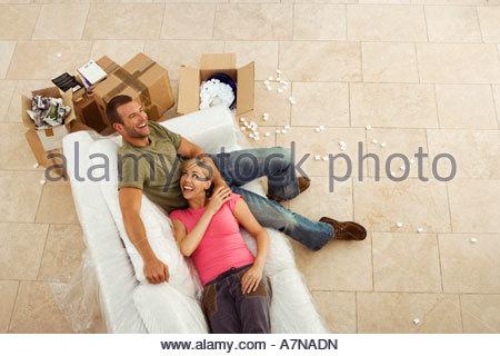Paar bewegliches Haus ruht auf weißen Sofa neben Boxen Pause lächelnd Draufsicht - Stockfoto