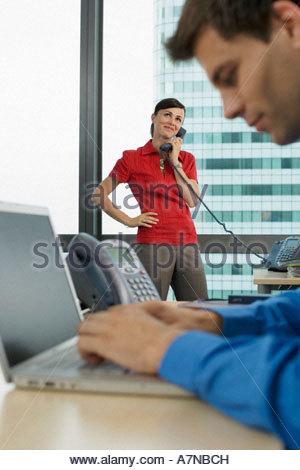 Geschäftsmann mit Laptop im Büro Fokus auf Frau mit Telefon im Hintergrund lächelt Seitenansicht - Stockfoto