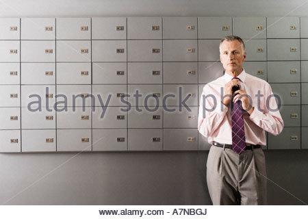 Reife Geschäftsmann lila Krawatte stand vor Zeile der Schließfächer Vorderansicht Porträt einstellen - Stockfoto