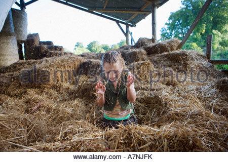 Mädchen 7-9 spielen unter Heu in der Scheune lächelnd Frontansicht - Stockfoto
