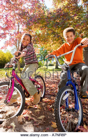 Jungen und Mädchen 7 9 sitzen auf Fahrrädern im Herbst Park, Lächeln, Porträt - Stockfoto