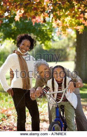 Mädchen 7 9 sitzen auf dem Fahrrad neben Mutter und Großmutter im Herbst Park senior Frau umarmt Enkelin Porträt - Stockfoto