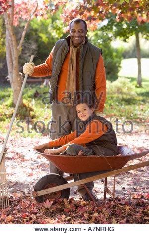 Ältere Mann und Enkel 7-9, die Blätter sammeln im Herbst im Garten Junge sitzt in der Schubkarre, Lächeln, Porträt - Stockfoto