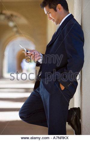 Geschäftsmann, stehen beim Aufbau Arcade betrachten SMS auf Handy lächelnd Profil - Stockfoto