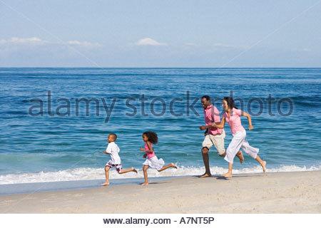 Familie, Sandstrand in der Nähe von Wasser s Rand Atlantischen Ozean im Hintergrund-Seitenansicht - Stockfoto