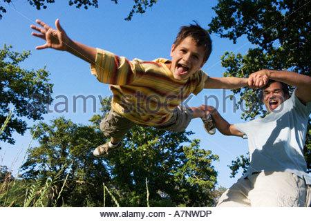 Vater schwingenden Sohn 9 11 im Wald Lichtung Jungen schreien niedrigen Winkel Ansicht tilt - Stockfoto