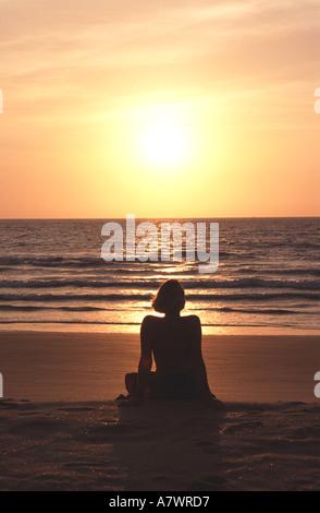 GOA, INDIEN. Eine junge Frau meditiert beim Sonnenuntergang am Colva Strand von Benaulim. - Stockfoto
