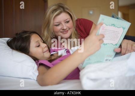Mutter, sieben Jahre altes Mädchen im Bett lesen - Stockfoto