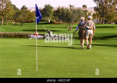 Älteres Paar in 70er Jahren wandern Putting green zusammen am Golfplatz in Palm Springs, Kalifornien - Stockfoto