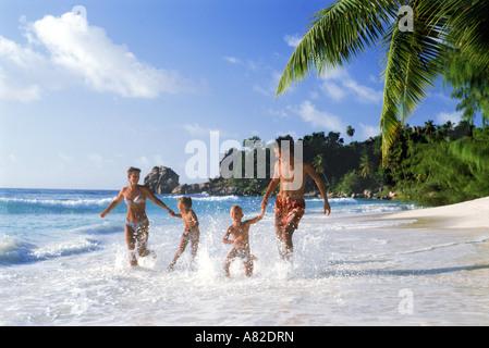 Vierköpfige Familie laufen durch Ufer Wellen auf der Insel La Digue auf den Seychellen - Stockfoto