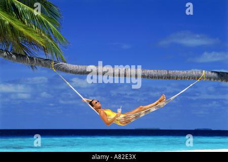 Frau in Hängematte unter Palmen Baum und blauen Himmel mit tropischen Drink entspannen - Stockfoto
