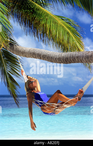 Frau mit Sonnenbrille zum Entspannen in der Hängematte unter Palmen - Stockfoto