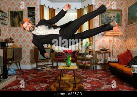 In der Luft Mann gekleidet in einen Anzug fallen horizontal in einem Wohnzimmer - Stockfoto
