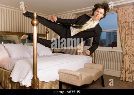 In der Luft Mann im Anzug fallen horizontal in einem Schlafzimmer - Stockfoto